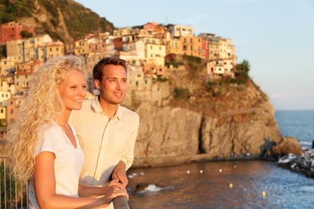 cinque: Romantic couple in love by sunset on holidays travel. Young beautiful couple enjoying ocean view romance. Young people, man and woman traveling on vacation in Manarola, Cinque Terre, Liguria, Italy