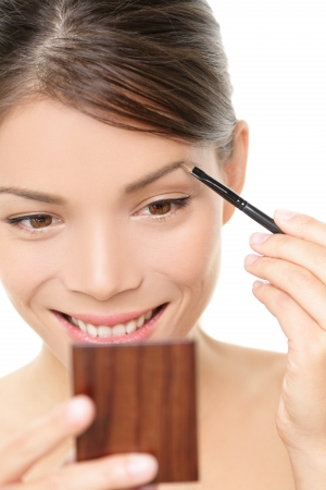 Makeup girl putting eyebrow color looking in pocket mirror  Smiling happy young beauty woman applying make-up with eye brow brush holding pocket mirror isolated, white background  Asian Caucasian girl photo