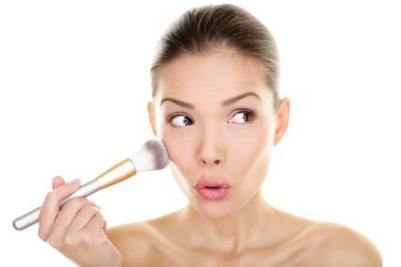 Makeup blozen schoonheid vrouw op zoek grappig weg naar kant Verrast schattig schattig meisje toepassing van make-up op de wangen make-up borstel opzij Gemengd ras Aziatisch Chinees Kaukasische model, jaren '20, geïsoleerd