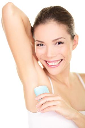 sudando: Desodorante - mujer de aplicar el desodorante en la axila Belleza poniendo desodorante antitranspirante en barra en las axilas sonriendo feliz aislado en el fondo blanco Raza mixta asiática caucásica mujer