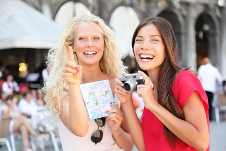 Tourist travel women friends with camera and map  Tourism concept with woman girlfriends having fun on summer holidays vacation on Piazza San Marco Square, Venice, Italy  Multicultural friends  photo