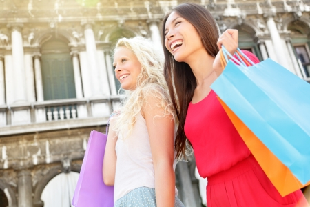 Shopping women happy holding shopping bags walking having fun laughing in street  Beautiful young Asian woman and Caucasian woman girlfriends on travel vacation, Piazza San Marco Square, Venice, Italy Stock Photo - 22482752