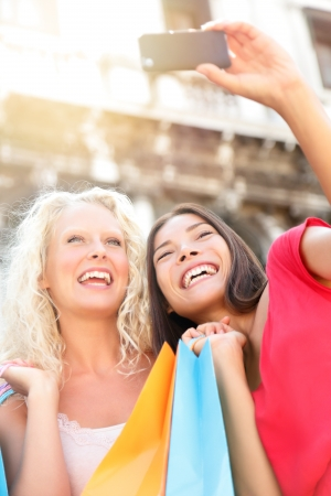 Girlfriends shopping laughing happy taking photo with smartphone  Woman friends holding shopping bags while taking self-portrait picture outdoor  Blonde girl and multiracial Asian Caucasian woman, 20s photo