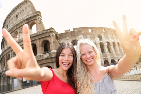 Travel tourist girl friends by Colosseum, Rome  Happy girlfriends tourists showing victory hand sign gesture in front of Coliseum  Beautiful young happy blonde girl and multiracial Asian woman, Italy  Stock Photo