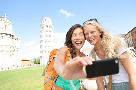 leaning tower of pisa: Travel tourists friends laughing taking photo with smartphone  Women girlfriends traveling in Europe smiling joyful having fun taking self-portrait picture in Pisa by Leaning Tower of Pisa, Italy