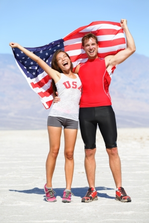 Cheering people athletes holding american USA flag celebrating happy with winning gesture after running. Young multicultural fitness runner couple in excited celebration outside in warm desert nature. photo