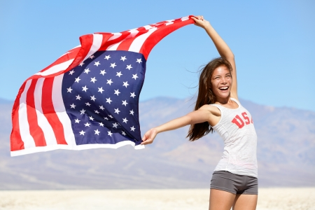winning flag: American flag - woman USA sport athlete winner cheering waving stars and stripes outdoor after in desert nature. Beautiful cheering happy young multicultural girl joyful and excited.