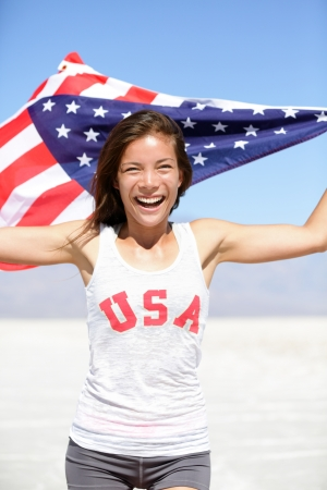 Athlete woman with american flag and USA t-shirt running showing winning gesture excited and happy outdoor in desert nature. Cheerful fitness woman winner cheering. photo