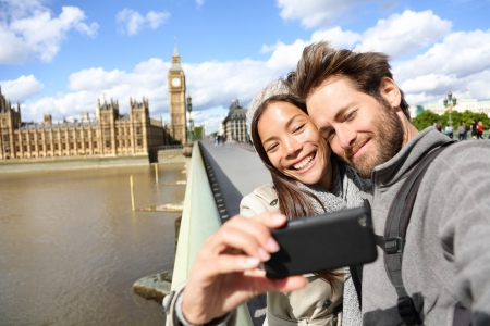 London tourist couple taking photo near Big Ben. Sightseeing woman and man having fun using smartphone camera smiling happy near Palace of Westminster, Westminster Bridge, London, England. Stock Photo