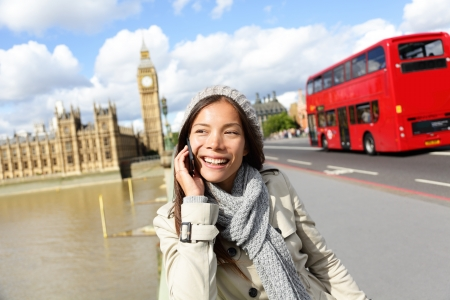 english girl: London - professional business woman on smartphone smiling happy. Young happy casual woman talking on smart phone walking outdoor in fall or winter on Westminster Bridge, London, England. Asian model.