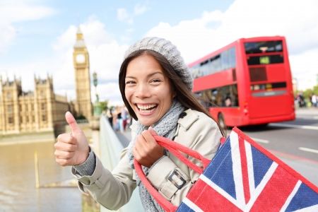 traveling: London tourist woman holding shopping bag near showing thumbs up sign happy excited near Big Ben. Shopper smiling on travel vacation in London. Asian Caucasian female traveler on Westminster Bridge.