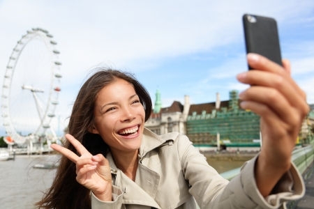 Asian tourist in London taking self-portrait photo smiling happy showing victory v hand sign with London Eye in background. Travel and tourism concept with beautiful girl travelling in London, England. photo