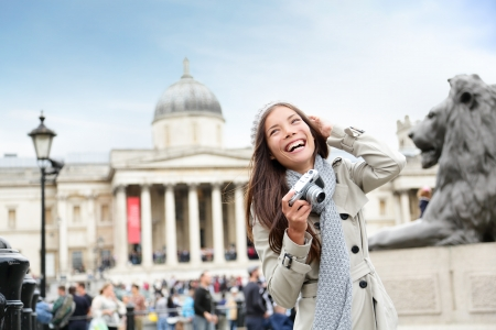 London tourist woman on Trafalgar Square in front of National Gallery taking photo holding camera smiling happy laughing having fun. Beautiful girl on travel vacation, London, England, United Kingdom. Stock Photo