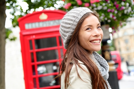 business: London people - woman by red phone booth. Portrait of beautiful smiling happy young female casual professional business woman walking outside in City of Westminster, London, England, Great Britain.