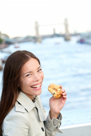 scone: Scones - woman eating scone in London. Happy girl holding British pastry by River Thames, London, England, United Kingdom Stock Photo