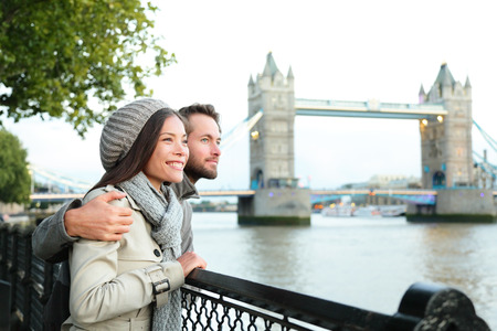 reizen: Gelukkige paar op Tower Bridge, Theems, Londen. Romantische jonge paar genieten van uitzicht tijdens reizen. Aziatische vrouw, blanke man in Londen, Engeland, Verenigd Koninkrijk.