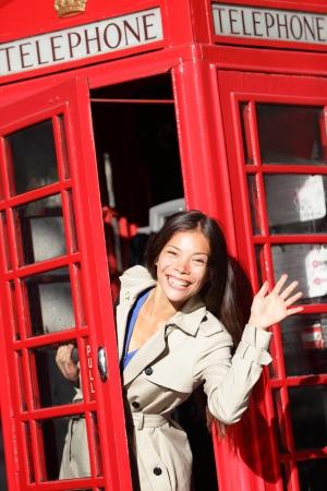 cabina telefonica: London rojo cabina telef�nica - mujer agitando feliz que enarbola emocionada mirando a la c�mara diciendo hola. Hermosa mujer sonriente joven en Londres, Inglaterra, Reino Unido. Foto de archivo