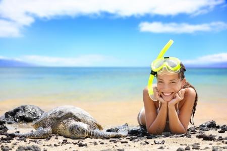 snorkelling: Beach travel woman on Hawaii with sea sea turtle. Snorkeling girl on vacation wearing snorkel smiling happy enjoying blue sky and sun lying next to Hawaiian sea turtles on Big Island, Hawaii, USA. Stock Photo