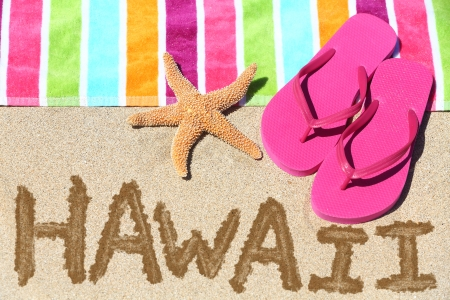 Hawaii beach travel concept. Hawaii written in sand with water next to beach towel and summer sandals and starfish. Hawaiian vacation holidays photo. photo