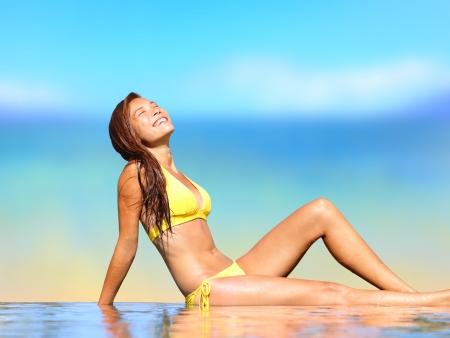 Sunbathing woman relaxing under sun in luxury spa retreat resort. Woman tanning enjoying sun in infinity pool in infinity pool by beach. Happy smiling mixed race Asian Caucasian girl in bikini, Hawaii photo