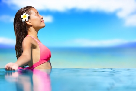 Spa vacation retreat woman relaxing at luxury travel resort. Happy blissful asian young woman in bikini in meditation enjoying summer sun and tanning during holidays on Hawaii. photo