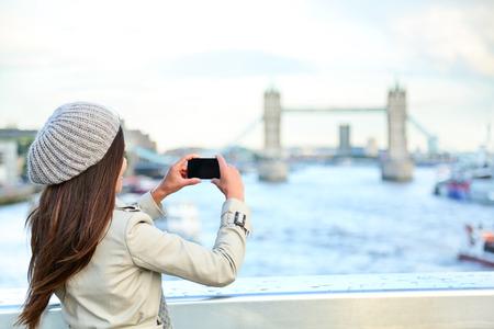 ロンドンの女性観光写真を取るタワー ブリッジのモバイルのスマート フォンのカメラで。景色を楽しみながら、テムズ川、ロンドン、イングランド