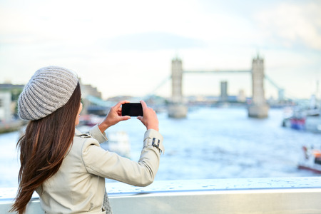 taking photo: London woman tourist taking photo on Tower Bridge with mobile smart phone camera. Girl enjoying view over the River Thames, London, England, Great Britain. United Kingdom tourism concept.