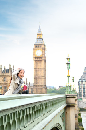 winter palace: London woman happy by Big Ben laughing and drinking coffee in fall or winter. Young female professional on Westminster Bridge, London, England. Beautiful young multiracial Asian Caucasian girl. Stock Photo