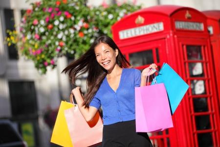 cabina telefonica: Mujer de las compras en Londres caminar sosteniendo bolsas de compras felices. Alegre hermosa shopper multirracial frente a cabina de tel�fono rojo. Westminster, Londres, Inglaterra, Reino Unido. Asiatico de C�ucaso. Foto de archivo