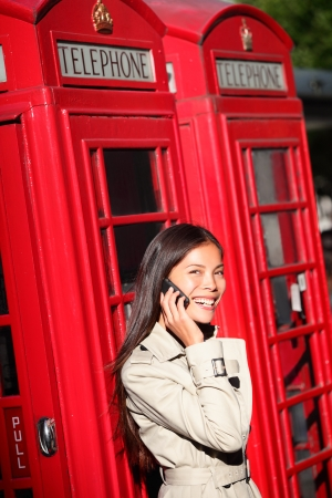 cabina telefonica: Mujer que toma el teléfono inteligente de London rojo cabina telefónica. Mujer de negocios casual femenino joven que tiene una conversación en el teléfono móvil inteligente en Londres, Inglaterra, Reino Unido. Multirracial asiáticos caucásica modelo Foto de archivo