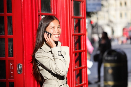 London business woman on smart phone by red phone booth. Communication concept with young multiracial Asian businesswoman on smartphone or mobile phone in London, England, United Kingdom. photo