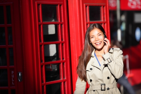 London woman taking on smart phone by red phone booth. Young casual female business woman walking with mobile phone smartphone in London, England, United Kingdom. Multiracial Asian Caucasian model. photo