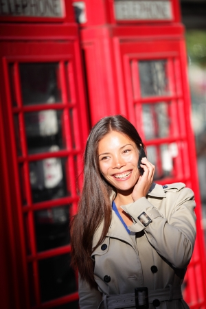 London woman taking on smartphone by red phone booth. Young casual female business woman having conversation on mobile smart phone in London, England, United Kingdom. Multiracial Asian Caucasian model photo