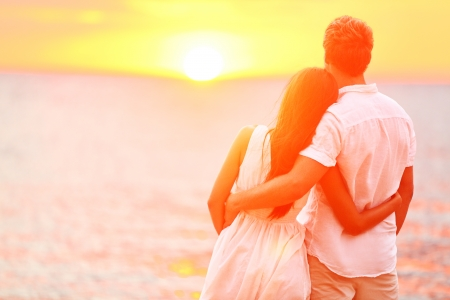 Honeymoon couple romantic in love at beach sunset. Newlywed happy young couple embracing enjoying ocean sunset during travel holidays vacation getaway. Interracial couple, Asian woman, Caucasian man. Banque d'images
