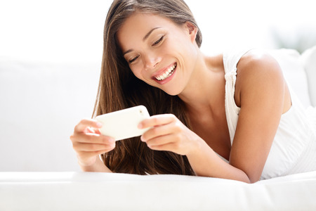 telefonok: Smartphone nő használ app Mobile okostelefon mosolyogni boldog. Szép többnemzetiségű lány sms szöveges üzenetküldés vagy a kérelem fekve a kanapén. Ázsiai, kaukázusi, modell az ő 20-as évek. Stock fotó