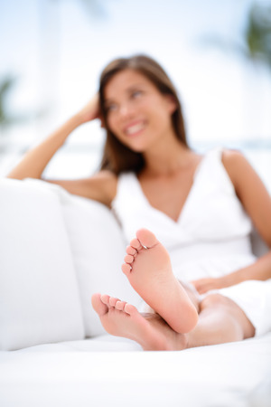 female feet: Woman feet - barefoot woman relaxing in sofa. Closeup of female feet of young beautiful woman sitting in couch outside. Stock Photo