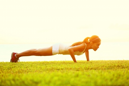 Push ups or press ups exercise by young woman. Girl working out on grass crossfit strength training in the glow of the morning sun against a white sky with copyspace. Mixed race Asian Caucasian model. Stock Photo