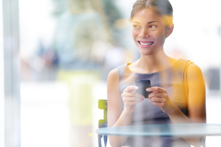 City lifestyle business woman using smartphone on cafe. Young professional female businesswoman on smart phone while sitting indoors in cafe looking out. Multicultural Asian Caucasian girl in her 20s. Stock Photo - 22672806