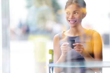 lifestyle: Stadsleven zakelijke vrouw met behulp van smartphone op cafe. Jonge professionele vrouwelijke onderneemster op slimme telefoon tijdens de vergadering binnen in cafe uitkijken. Multiculturele Aziatische Kaukasische meisje in haar jaren '20.