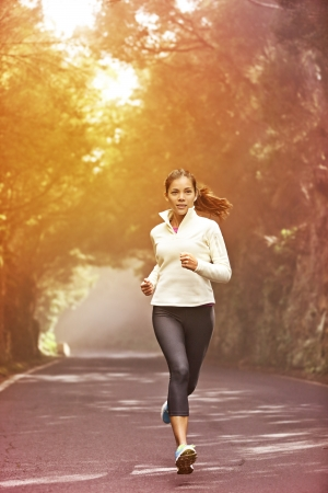 morning: Young woman running. Female runner jogging on misty road with the early morning at sunrise with sun breaking through the trees as she trains during a fitness workout. Stock Photo