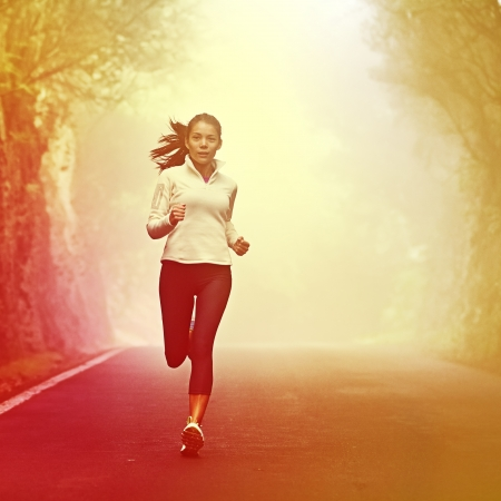 Running woman jogging on road in sunrise and mist. Female runner working out in fall or winter sports outfit. Beautiful multiracial Asian Caucasian woman athlete outside. Imagens