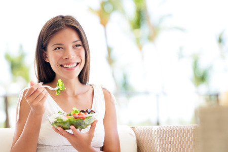 eat: Healthy lifestyle woman eating salad smiling happy outdoors on beautiful day. Young female eating healthy food outside in summer dress laughing and relaxing in sofa. Pretty multiracial model.