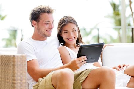 Paar ontspannen samen in bank met tablet-computer pc plezier. Romantische jonge gelukkige multiraciale paar in liefde zit thuis in sofa rusten voor de lol misschien kijken naar film. Man en vrouw.