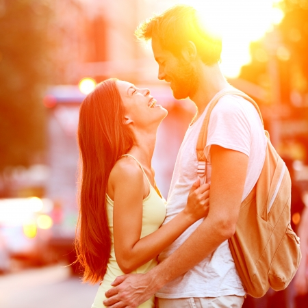 love kissing: Couple in love kissing laughing having fun. Dating interracial young couple embracing on date. Caucasian man, Asian woman on Manhattan, New York City, USA.