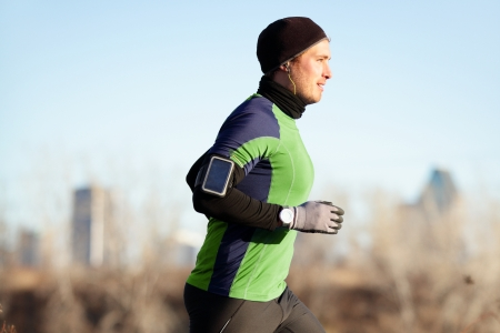 fit man: Running man jogging in autumn listening to music on smart phone. Runner training in warm outfit on cold day. Fit male fitness athlete model training outdoor in fall. Full body length of jogger. Stock Photo
