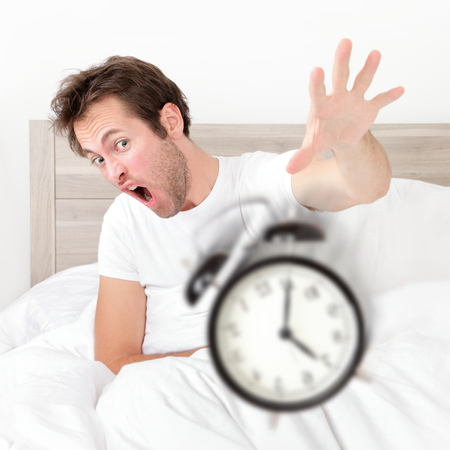 deprivation: Man waking up late for work early throwing alarm clock. Funny bed concept with young man oversleeping. Stock Photo