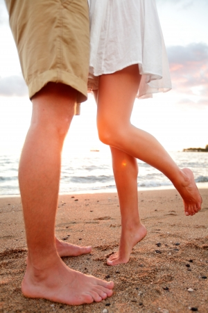Love - romantic couple dating on beach kissing and embracing. Happiness and romance travel concept with happy young couple barefoot in sand enjoying beautiful sunset. photo