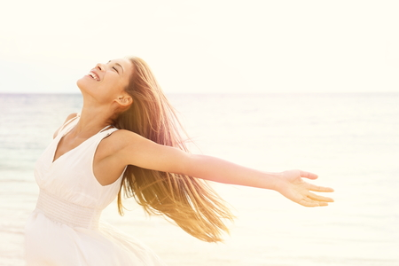 worship white: Freedom woman in free happiness bliss on beach. Smiling happy multicultural female model in white summer dress enjoying serene ocean nature during travel holidays vacation outdoors.