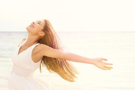 Vrijheid vrouw in vrije geluk zaligheid op het strand. Lachend gelukkig multiculturele vrouwelijk model in witte zomerjurk genieten serene oceaan, natuur tijdens vakantiereizen vakantie buitenshuis.