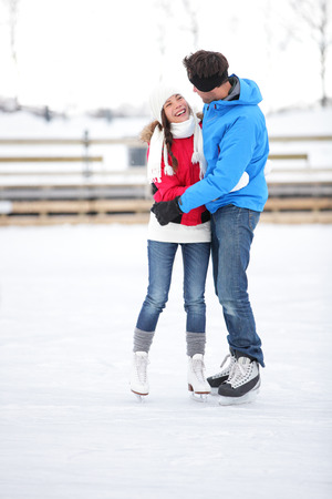 skating rink: Ice skating couple on date in love iceskating and embracing. Young couple embracing on ice skates outdoors on open air rink in snowy winter landscape. Multiracial couple, Asian woman, caucasian man